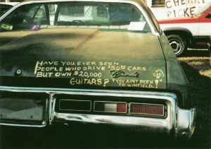 """""""Have you ever seen people who drive $0 cars but own $20,000 guitars? You ain't been to Winfield!"""" (Postcard front)"""