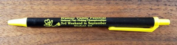 """Black and Yellow pen with Walnut Valley Festival's """"Fesity"""" logo and contact information"""