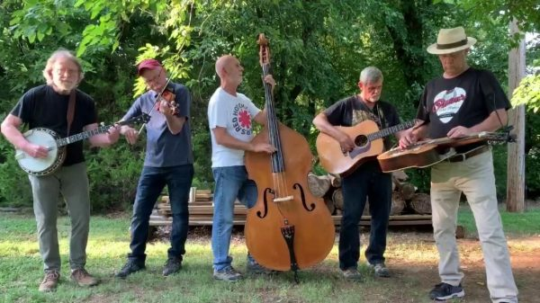 "Members of ""Dalton City Limits"" playing their instruments outdoors"