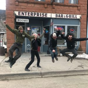 """Members of the """"Foggy Memory Boys"""" jumping in the air in front of the Enterprise Bar & Grill"""
