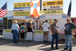 Roasted corn, turkey legs, and other foods for sale on the festival midway
