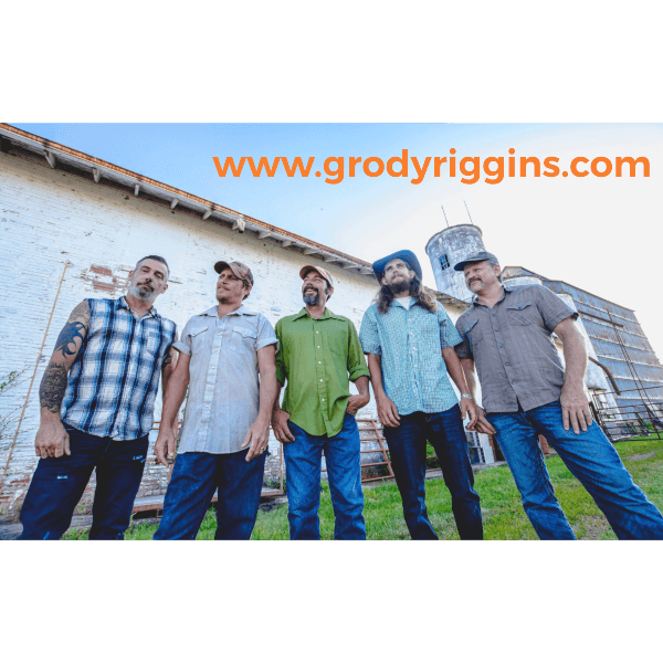 """Members of """"Grody Riggins"""" standing in front of a grain elevator"""