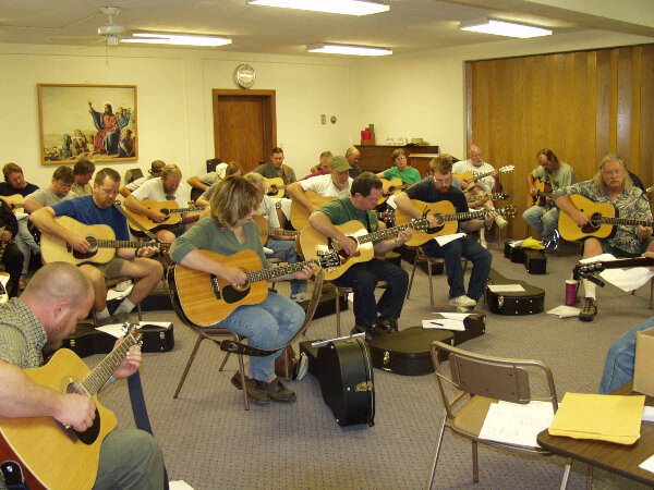 Group of students playing guitar during a workshop