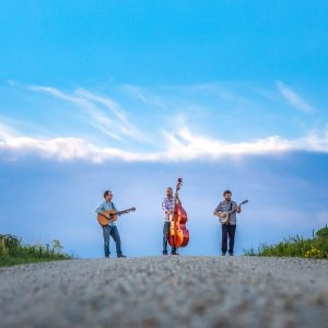 "Members of ""Old Sound"" standing on a road playing instruments"