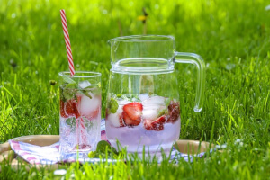 Iced strawberry water in cup and pitcher