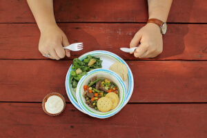 Person at picnic table ready to eat