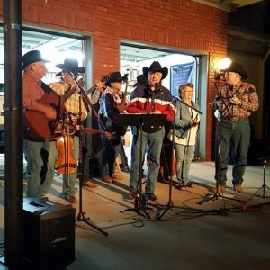 """Members of """"The Burnt Ends"""" playing an outdoor concert"""